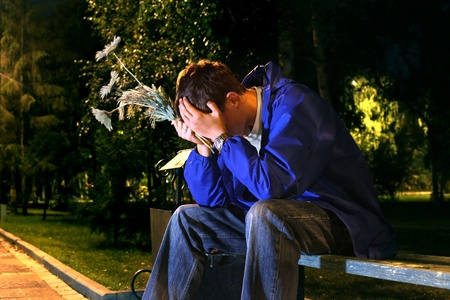 very sad teenager with a flowers in the night park get break an appointment photo