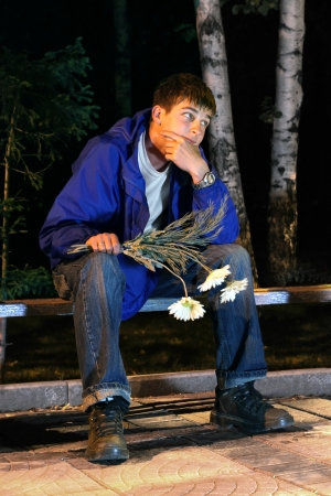 sad teenager with flowers waiting for a girl. unsuccessful appointment concept Stock Photo - 11679084