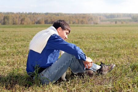 handsome teenager sitting in the field photo