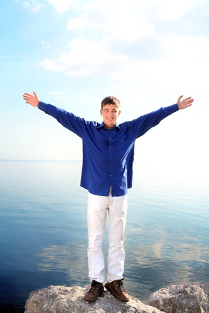 happy young man with hands up on the seaside background photo