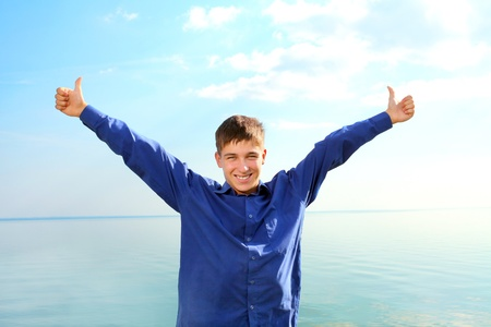happy young man spread hands with thumbs up on the seaside background in the sunny day photo
