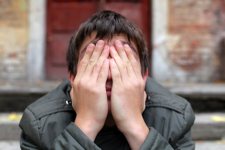 agitation: man with hidden face on the old house background Stock Photo