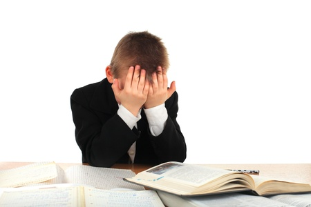tired schoolboy on the table isolated on the white background photo