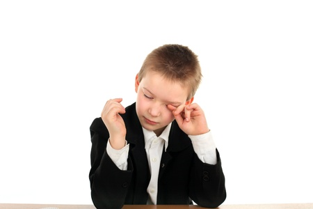 discontent: very sad schoolboy crying on the table isolated on the white background
