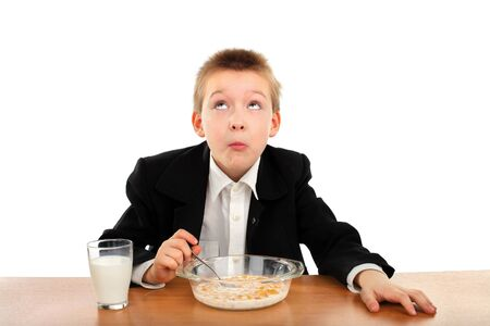 starvation: schoolboy eating corn flakes isolated on the white