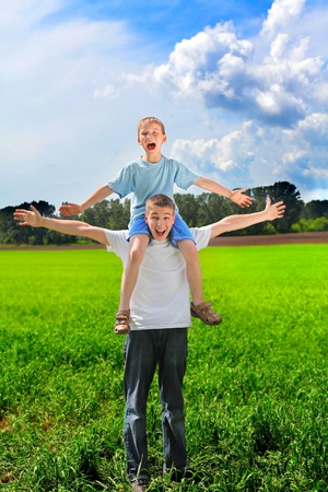 shoulder ride: happy young man and boy in the summer field Stock Photo