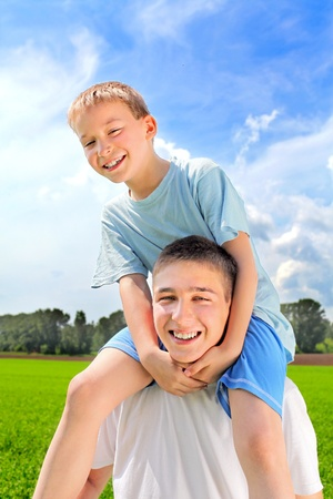 happy young man and boy in the summer field Stock Photo