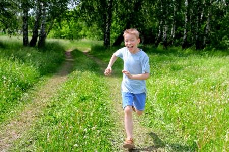 ni�o corriendo: ni�o feliz corriendo en el bosque de verano Foto de archivo