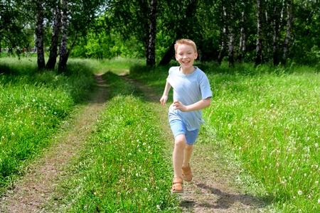 pantalones cortos: ni�o feliz corriendo en el bosque de verano Foto de archivo