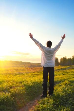 hombre orando: silueta de hombre feliz en el fondo puesta de sol