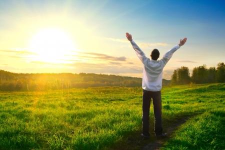 hombre orando: hombre feliz con las manos sobre fondo puesta de sol