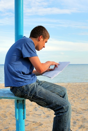 teenager reading letter on the empty beach Stock Photo - 13329079
