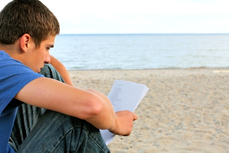 teenager reading letter on the empty beach Stock Photo - 13329074