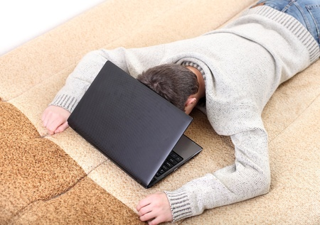 tired young man falling asleep with notebook on sofa