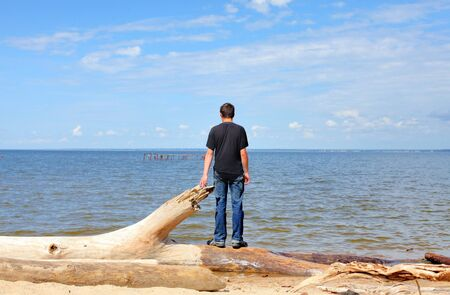 young man at seaside looking on the sea in the summer sunny day photo