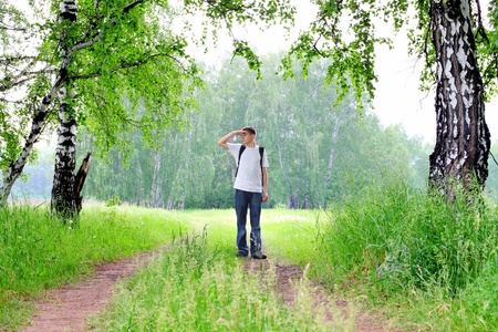 teenager with knapsack get lost in summer forest