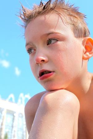 lost child: sad boy portrait outdoor after bathing