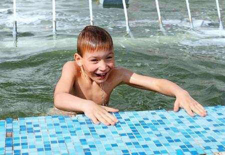 happy boy bathing in the fountain photo