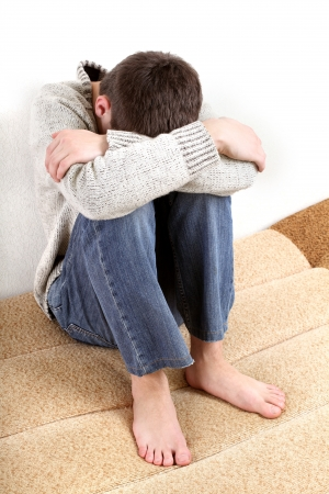 counterpane: sad teenager sitting on the bed in home interior Stock Photo