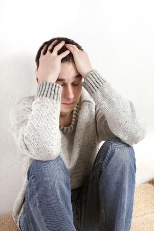uneasiness: hombre joven triste ocultar una cara de las manos Foto de archivo
