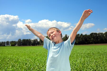 boy with hands up in the summer field photo