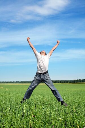 Happy young person jumping on the summer meadow photo