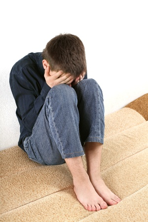 sad teenager sitting on the bed in home interior photo
