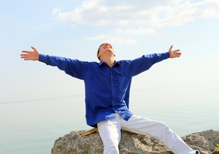 happy young man with hands up on the seaside background in the sunny day photo
