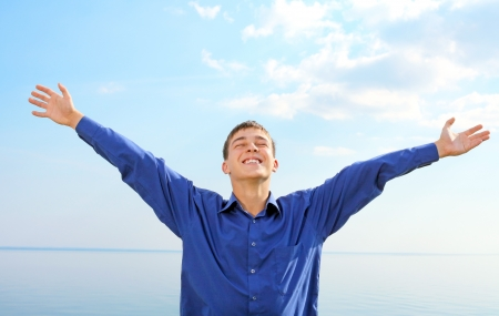 happy young man spread hands on the seaside background in the sunny day photo