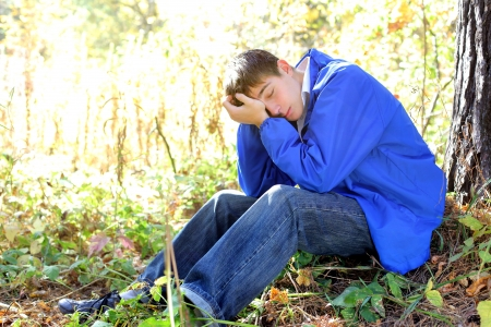 agitation: sad teenager sitting in the autumn forest alone