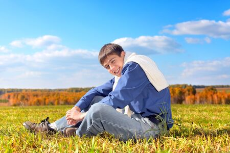 young man sitting in the autumn field photo
