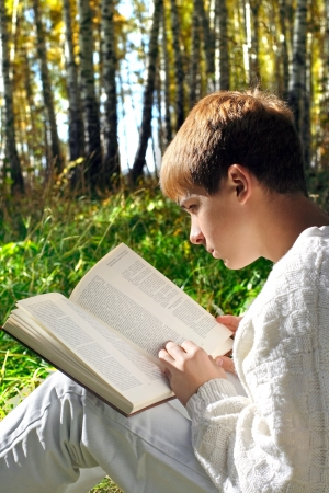teenage boy sit in autumn forest with a book photo