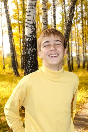 cheerful teenage boy portrait in autumn forest photo