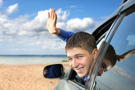 happy young man sitting in the car and wave goodbye Foto de archivo