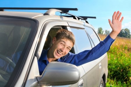 happy young man sit in the car and give salute gesture photo