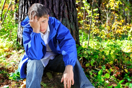 sorrowful teenager sitting in the autumn forest alone photo