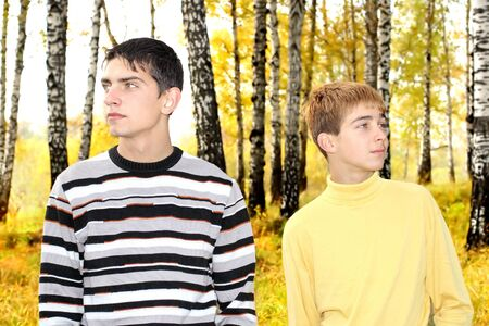 dissension: two teenage boys in the autumn park look in different directions