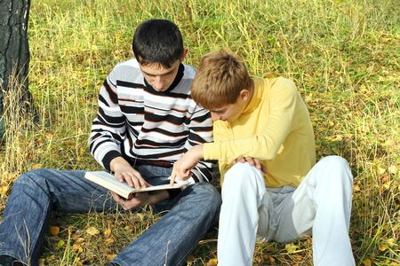boys sit in autumn forest with a book photo
