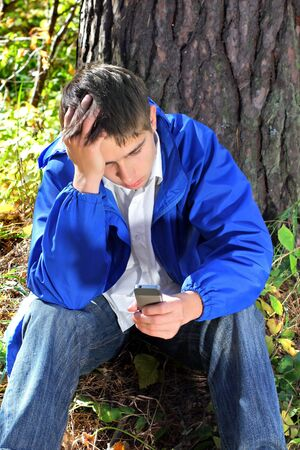 sad young man with mobile phone in the autumn forest alone photo