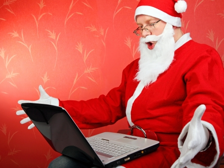 surprised santa claus get message on laptop computer  on the red background photo