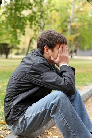 печальный: грустный молодой человек, сидящий в осеннем парке