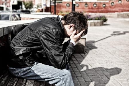 uneasiness: hombre joven triste que se sienta en la calle de la ciudad