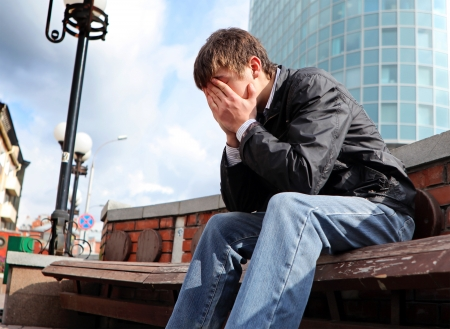 nervousness: sorrowful young man sitting on the city street Stock Photo