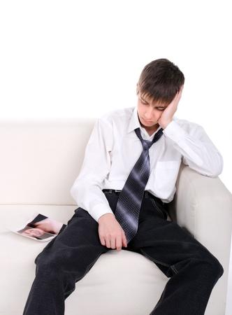 relaciones humanas: adolescente pensativo sentado en el sof� con una foto rasgada de su novia