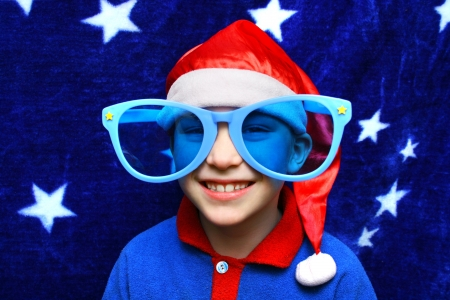Small Boy in Big blue Glasses on the Blue Curtain background photo