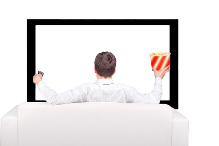big screen: Teenager with Remote Control and Popcorn sitting on the Sofa and watching Tv-set Stock Photo