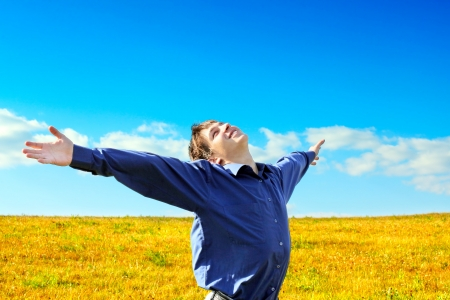 brunets: Happy Young Man raising his Hands in the Summer Field