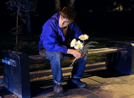 Sad Teenager in the Night Park with Flowers