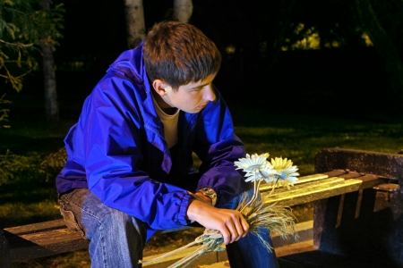 first date: Sad Teenager in the Night Park with Flowers