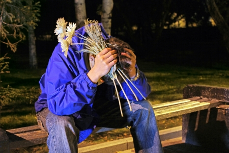 Troubled Teenager with a flowers and hidden face sitting in the night park photo